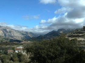 Die traumhafte Landschaft der Sierra de Castril - weisse Häuser - kahle Berge, darüber ein blauer Himmel mit weiss-grauen Wolken - Provinz Granada - Andalusien - Spanien