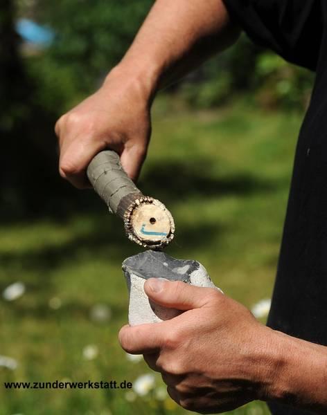 Steinzeitliche Feuersteinbearbeitung mit Hornschlegel zur Herstellungen von Pfeilspitzen und Speerspitzen