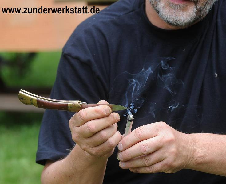 Glut wird aus dem Pneumatischen Entnommen Feuerzeug zum Feuermachen.  Fire Piston, Feuerpumpe, Kompressionsfeuerzeug