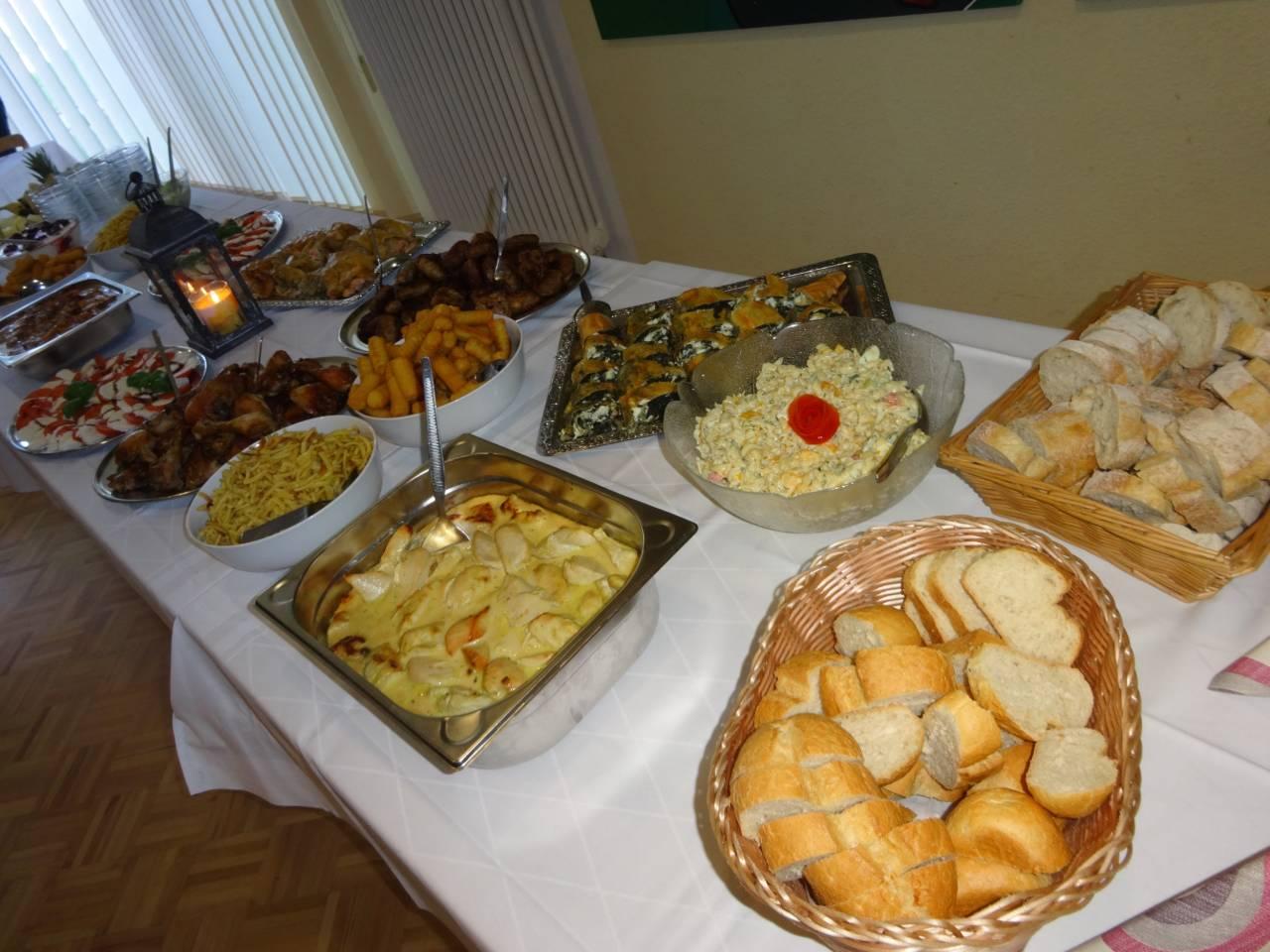Buffet-Angebot mit Baguette, Brötchen, Auflauf, Fleischspeisen, Tomaten-Mozarella, Kroketten, Nudeln, Joghurt, Obstschale