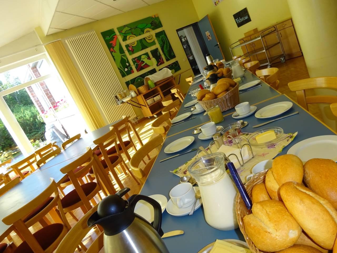 Frühstückstisch im Jugendhaus mit Brötchen, Kaffee, Milch, Aufstriche, Käse- und Wurstauswahl usw.