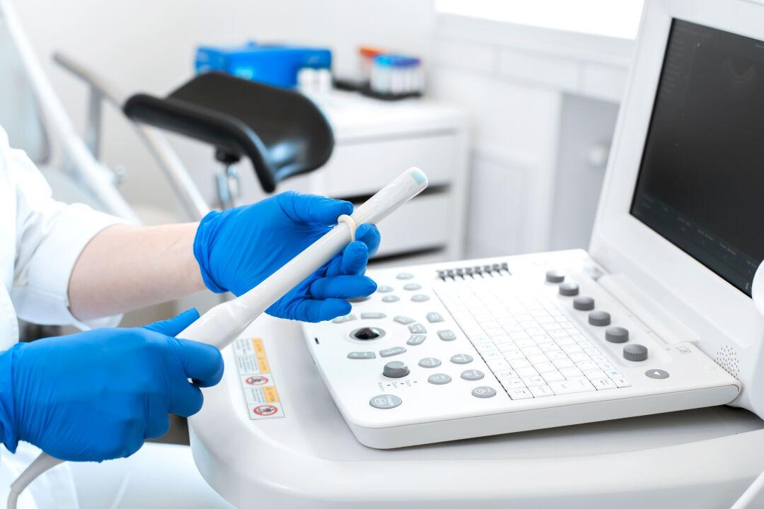 Ultraschallgerät, Untersucher legt Schutzhülle über die Ultraschallsonde