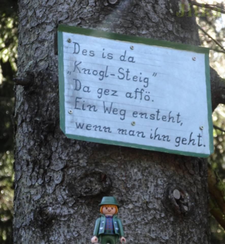 Foto von einem Schild im Wald auf dem steht: Des is da Knogl-Steig. Da gez affö. Ein Weg entsteht, wenn man ihn geht.