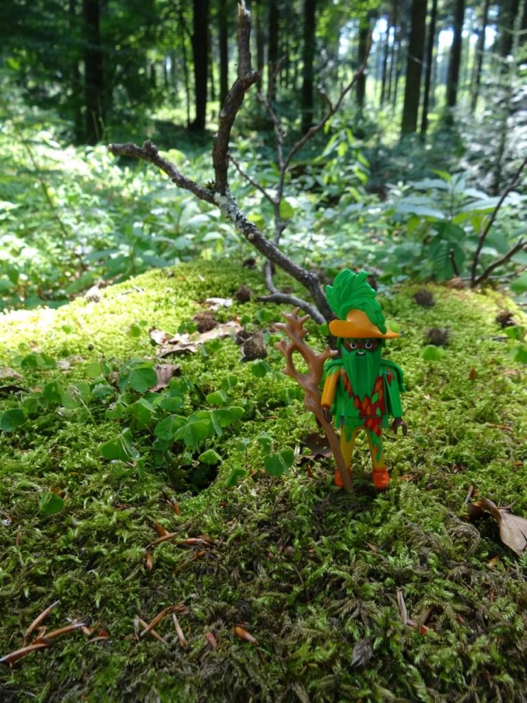 Foto: Playmobil (c) Figur Waldgeist auf einem bemoostem Stamm im Wald