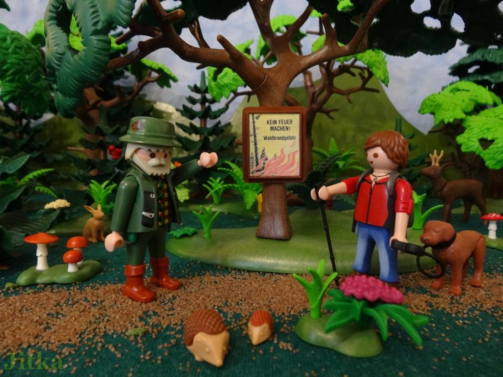 Bild: Förster zeigt einem Wanderer ein Schild im Wald auf dem steht: Kein Feuer machen! Waldbrandgefahr