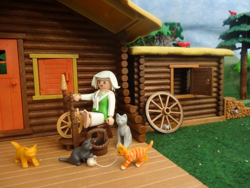 Die Großmutter sitzt vor der Hütte am Spinnrad. Die Kätzchen spielen mit dem Garn und ignorieren die Mäuse.