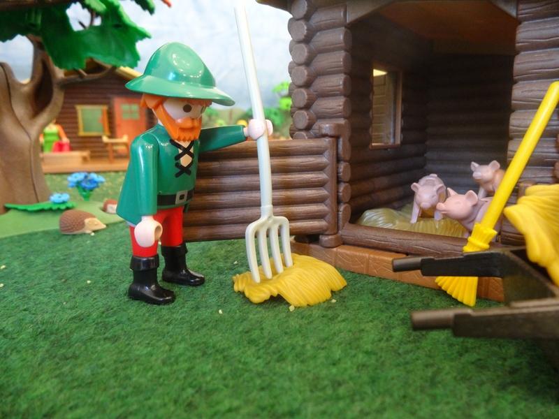 Der Bauer mistet den Schweinestall aus.