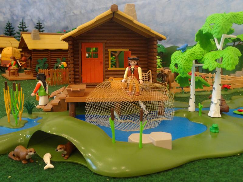 Der Fischer fischt mit einen Netz im Teich während die Fischotter einen Fisch fressen.