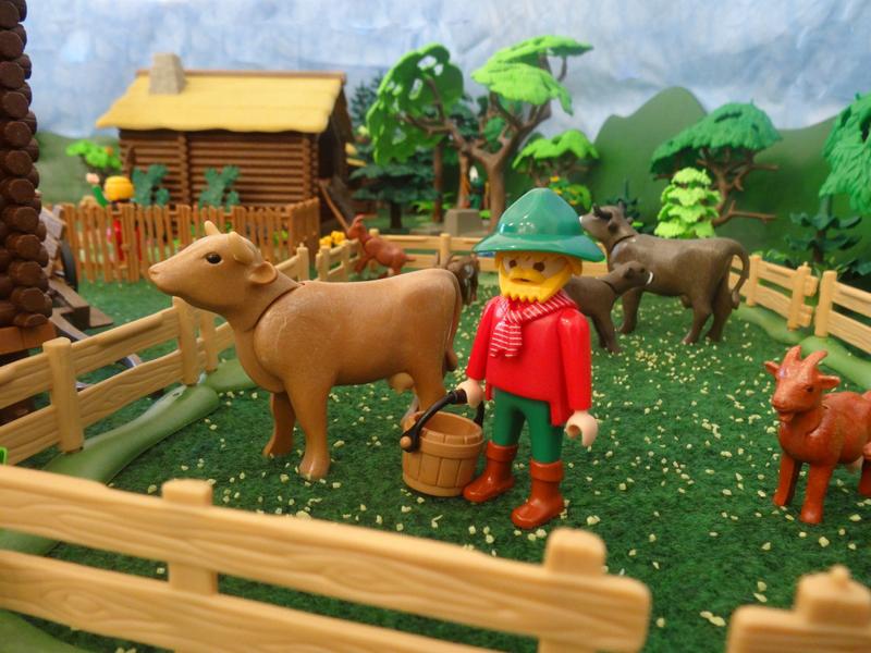 Ein Bauer auf einer Weide mit Kühen und Ziegen.