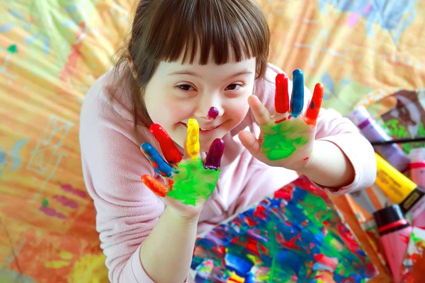 Fröhliches Farbenspiel eines Mädchens mit Trisomie21