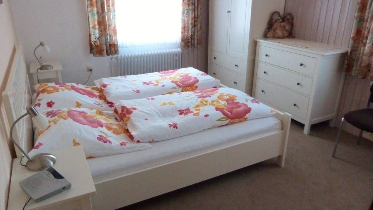 Das Nett Eingerichtete Schlafzimmer Ist Mit Einem Doppelbett,  Kleiderschrank, Kommode, Spiegel, Radiowecker Und 2 Stühlen Ausgestattet.