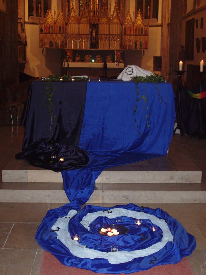 Mit blauen Tüchern und Teelichtern geschmückter Altar.