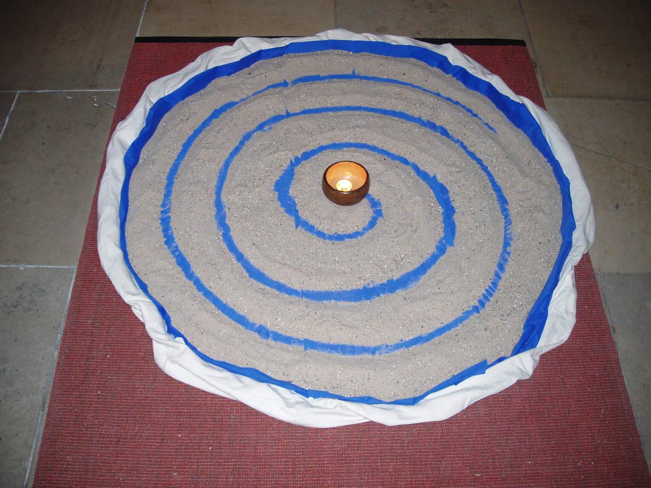 Mandala aus Sand und Tüchern.